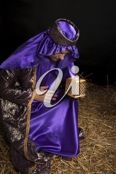 Wiseman from the east, bowing on bended knee and holding a gift of golden box filled with fine frankincense resin.