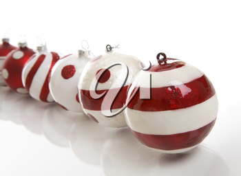 A selection of red and white Christmas baubles on a white background.  Focus is to first bauble.  Space for copy.