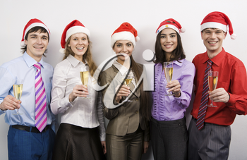 Portrait of joyful co-workers in Santa caps and champagne in hands looking at camera with smiles