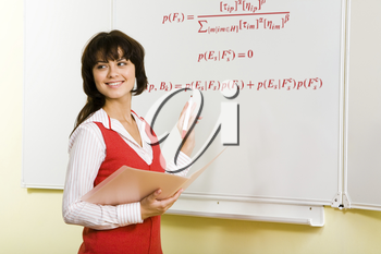 Image of attractive teacher writing formula on whiteboard during lesson