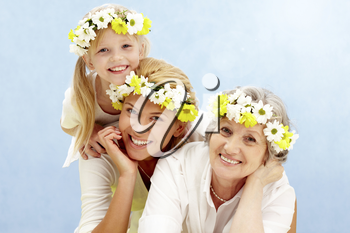 Portrait of daughter over her mother and grandmother with flowers on their heads