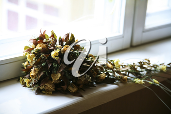 Photo of bouquet made up of withered flowers lying on window-sill