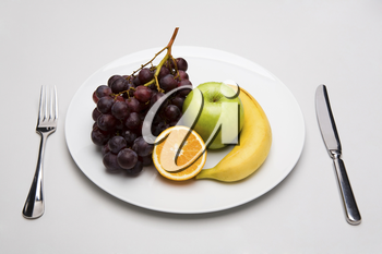 Fruit mix on white porcelain plate with fork and knife on both sides
