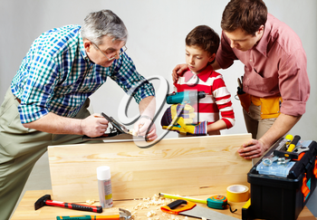 A grandfather and a father teaching a boy to work with plane