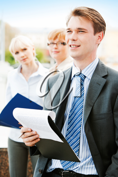 Portrait of serious boss holding pen over paper with young ladies at background