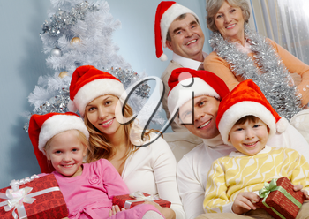 Portrait of happy young couple with two children wearing Santa caps on background of grandparents