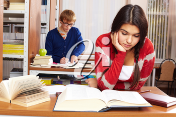 Portrait of young girl reading on background of guy in college library