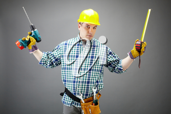 Portrait of architect worker with electric drill and measuring tape