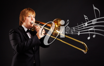 Portrait of young female playing the trombone on black background