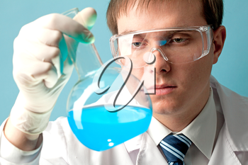 Serious clinician looking at flask with blue liquid in laboratory