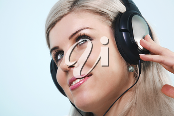 Headshot of a young pretty blond woman wearing headphones listening to music
