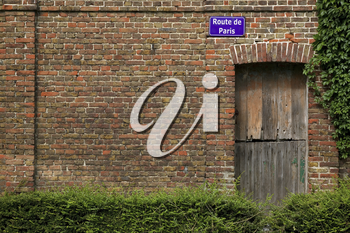 Road sign for Route de Paris on the side of an old French building