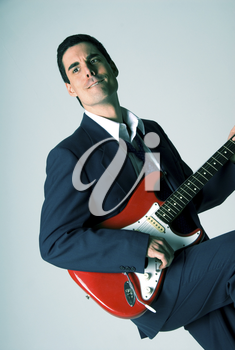 man in blue suit with a red guitar
