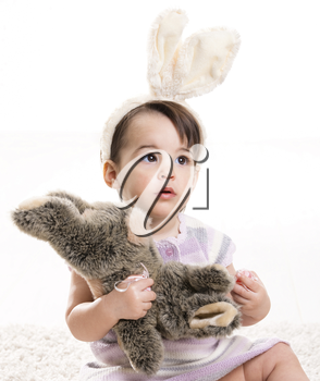 Baby girl in easter bunny costume, playing with toy rabbit, isolated on white background.