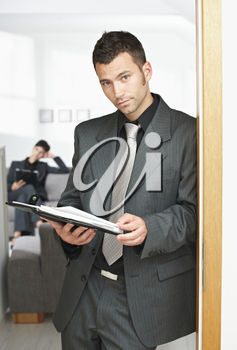 Young businessman standing in doorway at office, looking at organizer.
