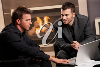 Businessmen working together at home, sitting in front of fireplace, using laptop computer.