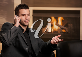 Businessman sitting in front of fireplace, talking on mobile phone, gesturing.