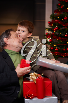 Portrait if happy grandfather and grandson holding christmas presents, cuddling.