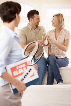 Estate agent holding for sale sign looking at celebrating couple holding champagne glasses in focus.