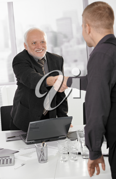 Senior executive shaking hands with businessman in office, smiling.