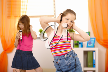 Girls enjoying music, listening via headphones, singing with microphone, dancing.