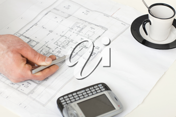 Architect's hand pointing with pen to a flooor plan on desk with mobile phone and coffee cup on it.