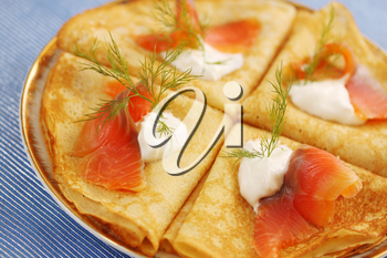 Roasted thin pancakes with smoked salmon and sauce