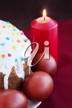 Easter cake with eggs and burning candle