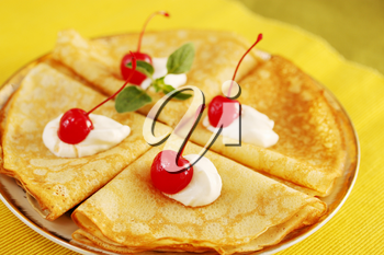 Pancakes with cream and cherries on a plate
