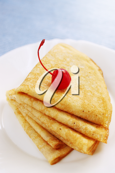 pile pancakes with cherries on a plate