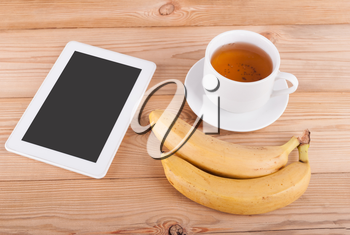 Digital tablet cup of tea and bananas on a wooden table.