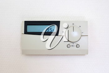 Digital Thermostat set to 19,5 degrees Celsius, isolated on white wall