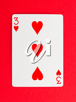 Old playing card (three) isolated on a red background