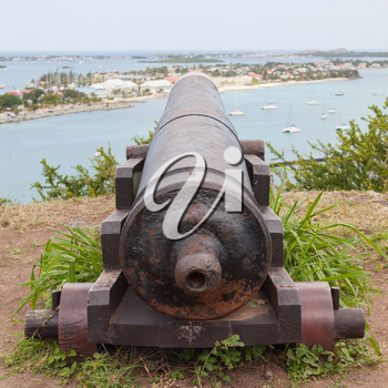 Very old rusted canon pointing at a bay, Caribbean