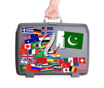 Used plastic suitcase with lots of small stickers, large sticker of Pakistan