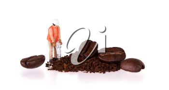Miniature worker with powerdrill working on a coffee bean