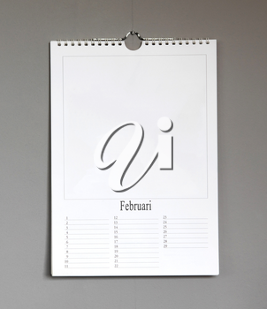 Simple old birthday calendar hanging on a grey wall, copy space - Februari