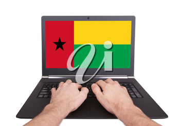 Hands working on laptop showing on the screen the flag of Guinea-Bissau