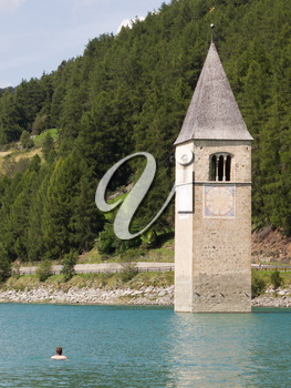 Submerged tower of reschensee church, man swimming next to it -  South Tyr or Alto Adige in Bolzano or bozen at Italy
