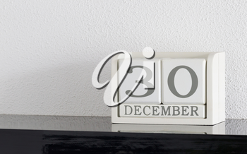 White block calendar present date 30 and month December on white wall background