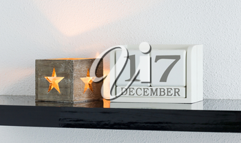 White block calendar present date 17 and month December on white wall background