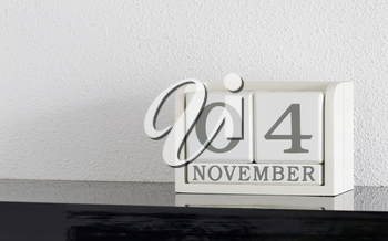White block calendar present date 4 and month November on white wall background
