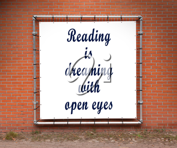 Large banner with inspirational quote on a brick wall - Reading is dreaming with open eyes