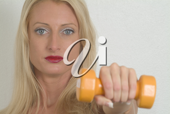 Stock Photo of a Woman Holding a Dumbell Weight In Front Of Her