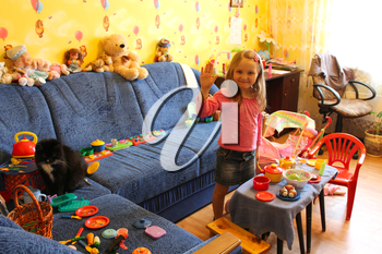 little girl playing with toys and cat in her room