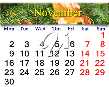 calendar for November of 2015 with the ribbon of yellow dry leaf on the evergreen spruce