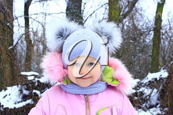 Portrait of smiling baby in amusing winter cap with two funny ears. Childhood is the best time