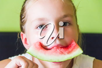 Photo of the cute girl eating watermelon