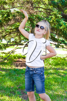 Photo of cute dancing girl with sunglass in summer