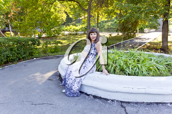 Pregnant woman with brown hair sitting in summer